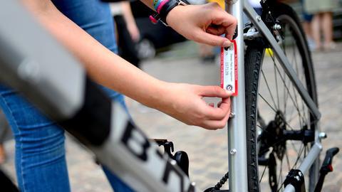 Eine Frau klebt eine Plakette mit einer registrierten Nummer auf den Rahmen eines Fahrrads.