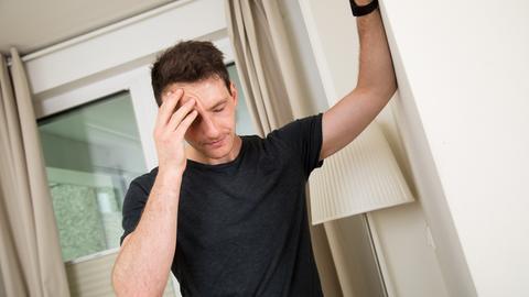 Ein Mann steht in einer Wohnung und stützt sich an einer Wand ab, weil er sich benommen fühlt.