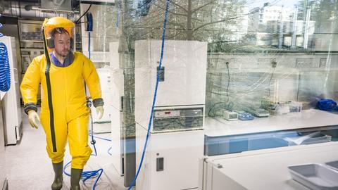 Ein Mitarbeiter arbeitet in einem Labor an Organismen im Hochsicherheitsbereich des Instituts für Virologie der Philipps-Universität Marburg.