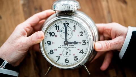 Zwei Hände halten einen alten Wecker. Es ist 03:00 Uhr.