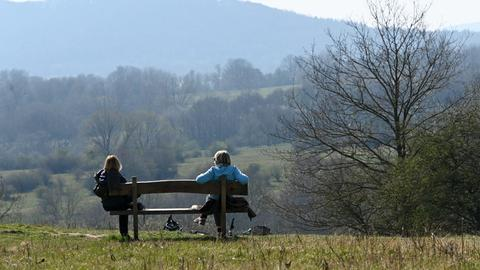 Zwei Frauen sitzen in gebührendem Abstand voneinander auf einer Parkbank am Rand des Naturschutzgebietes Dönche.