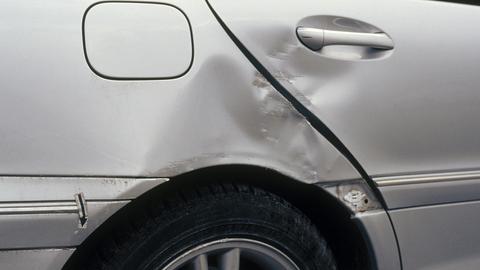 Beschädigte Hintertür und beschädigter Radkasten eines silbernen PKWs.