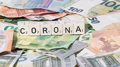 Viele Euroscheine und Scrabbelsteine, die das Wort Corona bilden.