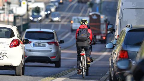 Ein Fahrradfahrer fährt auf einer stark befahrenen Straße.