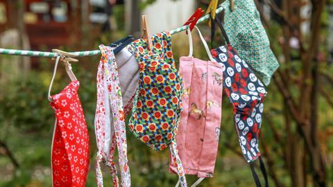 Gewaschene Mundschutzmasken hängen in einem Garten auf einer Wäscheleine.