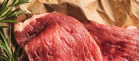 Rohes Kalbsfilet mit Salz- und Pfefferkörnern, Knoblauch und Rosmarin.