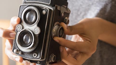 Hände halten eine antike Fotokamera.