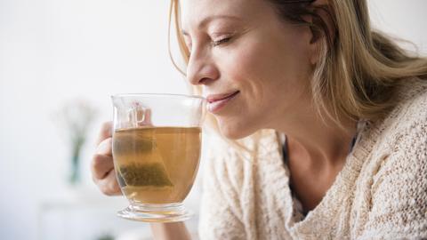 Eine Frau im Strickpullover riecht an einer Tasse Tee und lächelt dabei.