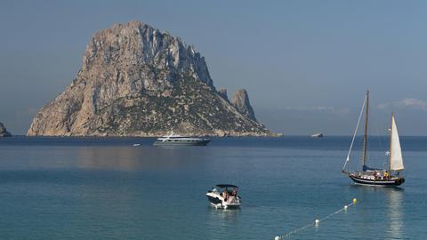 Es Vedra im Hintergrund, drei kleine Boote auf dem Meer im Vordergrund.