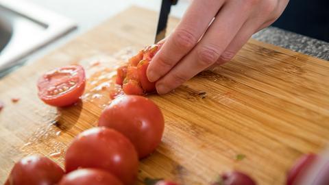 Eine Frau schneidet auf einem Holzbrett Tomaten klein.