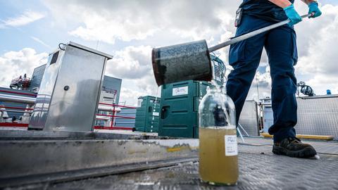 Eine Mitarbeiterin der Kläranlage entnimmt eine Probe des Abwassers. Das Wasser wird unter anderem auf Viruspartikel untersucht, um festzustellen, wie viele Menschen das Coronavirus unter den Mitgliedern haben und übertragen können.