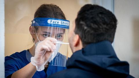 Eine Arzthelferin nimmt in einer Arztpraxis einen Abstrich für einen PCR-Corona-Test.