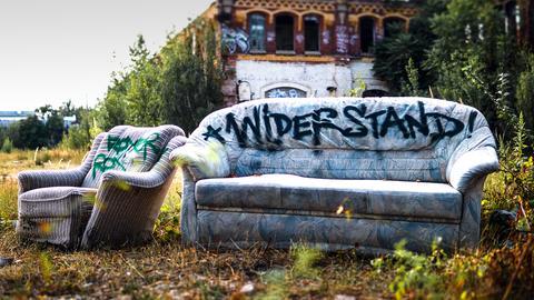 Eine weggeworfene Couch steht auf einer Wiese, im Hintergrund ein verlassenes Gebäude