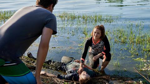 Das morgendliche Stand-up-Paddling von Jakob Frings (Max König, l.) und Julia Demmler (Wendy Güntensperger, r.) in der Liebesbucht findet ein jähes Ende, als Julia einen leblosen Körper am Ufer des Bodensees entdeckt.