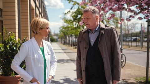 Dr. Kathrin Globisch (Andrea Kathrin Loewig) will Dr. Roland Heilmann (Thomas Rühmann) nach seiner Nachtschicht einen schönen Feierabend und etwas Schlaf wünschen.