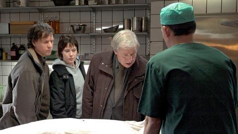 Van Veeteren (Sven Wollter 2. v. rechts) identifiziert im Beisein seiner Ex-Kollegen Münster (Thomas Hanzon, links) und Moreno (Eva Rexed) die Leiche seines Sohnes, der erschlagen wurde.