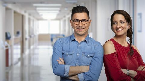Die Moderatoren Julia Tzschätzsch und Daniel Mauke vor einem Klinikflur