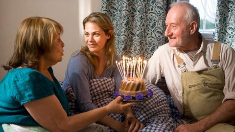 Hans (Sepp Schauer) und seine Frau Elisabeth (Petra Kelling) gratulieren ihrer Tochter Anna (Felicitas Woll, Mitte) zum Geburtstag.
