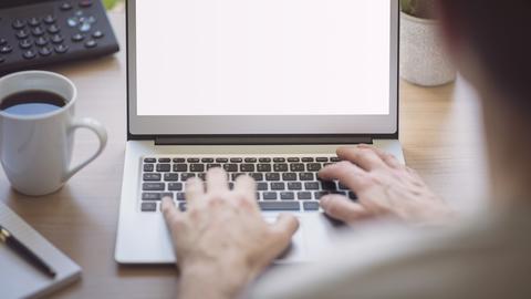 Behindert - und doch ein Recht auf Arbeit: Eine Person sitzt vor einem Laptop.