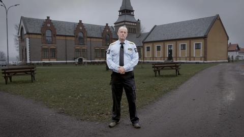Ein Gefängniswärter steht am Rande eines Gefängnishofs.