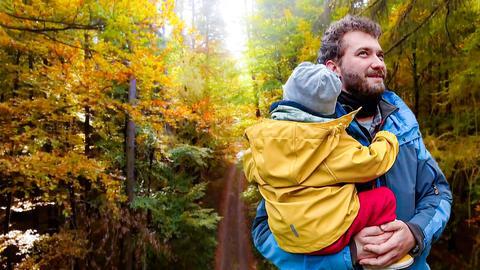 Mann hält Kind im Arm und steht im Wald.