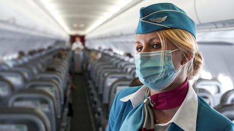Flugbegleiterin mit Mundschutz im Flugzeug.