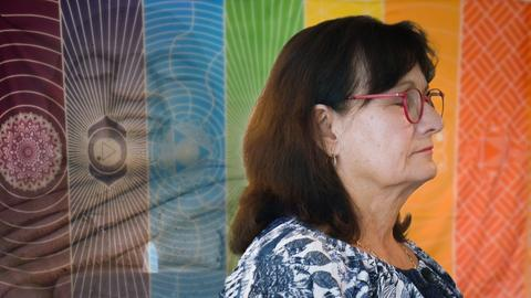 Protagonistin im Profil mit geschlossenen Augen, vor einem mehrfarbigen Wandteppich.