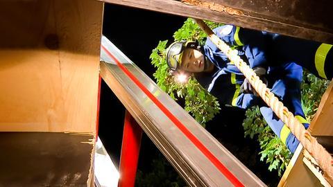 Eine THW'lerin schaut in ein Loch, in dem eine Leiter und ein Seil eingelassen sind.