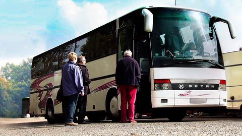 Mehrere Personen vor einem Reisebus