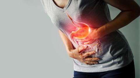 Eine Frau hält sich an ihrem Bauch und beugt sich leicht nach vorne. Mittels Computergrafik sieht man ihre inneren Organe.