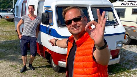 Friso Richter mit Sonnenbrille zeigt auf einen Schwimmcaravan.