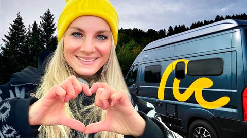 Maike Tschorn bildet mit ihren Fingern ein Herz, im Hintergrund der Campervan.