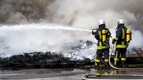 Zwei Feuerwehrleute löschen einen Brand