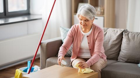 Eine ältere Frau sitzt in ihrem Wohnzimmer vor ihrem Tischchen mit einem Putzlappen in der einen und einem Schälchen voller Natron in der anderen Hand. Neben ihr stehen weitere Putzutensilien wie ein Eimer und ein Besen.