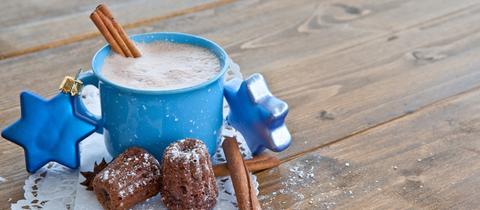 Eine blaue Tasse mit heißer Schokolade und einer Zimtstange auf Holzgrund. Zwei weitere Zimtstangen, zwei kleine Schokoküchlein und zwei blaue Sterne liegen um die Tasse herum.