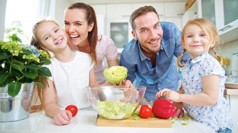 Glückliche Familie (Vater, Mutter und zwei Töchter) steht mit frischem Gemüse in der Küche.