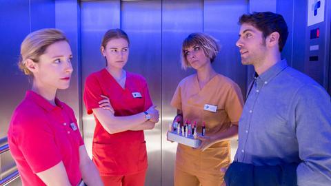 Dr. Niklas Ahrend (Roy Peter Link, r.) eröffnet Louisa (Llewellyn Reichman, 2.v.l.), vor Alexandra (Friederike Linke, l.) und Mo (Jaëla Carlina Probst, 2.v.r.) eine Chance, für ihren Krebspatienten Thomas Hauffe.