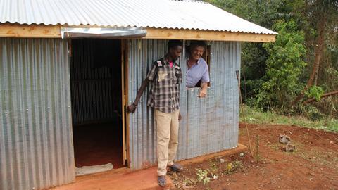 Fokko Doyen und John Kaheni stehen in beziehungsweise vor Johns Hütte.