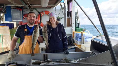 Heike Götz (Moderatorin) auf einem Ostsee-Kutter mit Matrose Stefan Mischke (links). Hier: vor frisch gefangenem Dorsch.