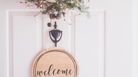 """Eine Haustür mit einem Schild """"Willkommen"""""""