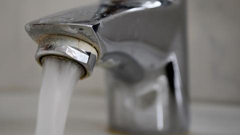 Wasser läuft aus einem verkalkten Wasserhahn.