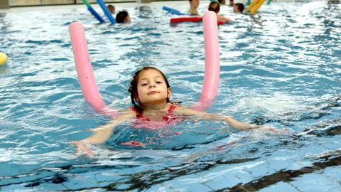 Ein kleines Mädchen hält im Schwimmbecken mithilfe einer Schwimmnudel den Kopf über Wasser.