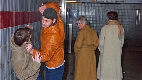 Wegschauen statt Zivilcourage: Zwei Passanten schauen weg, während ein Jugendlicher in einer U-Bahnstation einen anderen verprügelt. (Gestellte Aufnahme.)