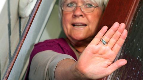 Eine ältere Frau öffnet mit abwehrender Handbewegung die Haustür.
