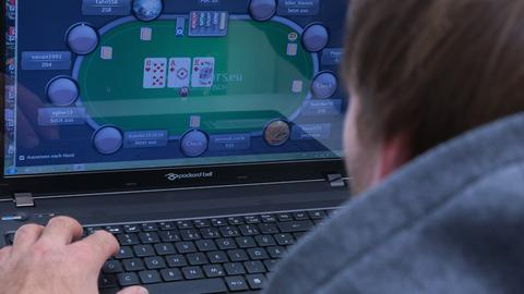 Ein Mann spielt an seinem Laptop ein Online-Pokerspiel.
