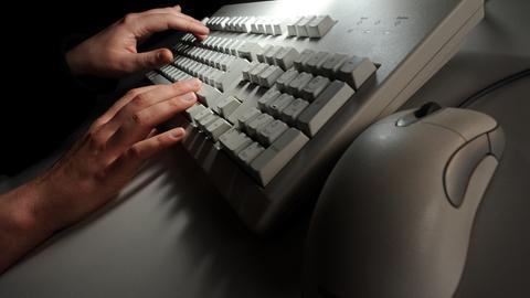 Hände tippen auf einer Computertastatur in einem abgedunkelten Raum.