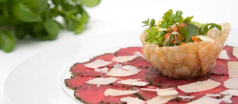 Ein Teller mit Rinder-Carpaccio und Parmesan und einer essbaren Schüssel mit Salat.