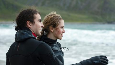 Lukas (Marlon Valdés Langeland) nimmt Karin (Mathilde Holtedahl Cuhra) zum Surfen mit – trotz des gefährlichen Wellengangs.