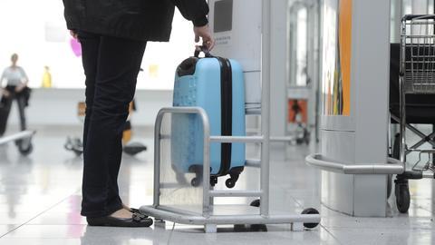 Eine Frau prüft am Flughafen an einer Prüfstelle für Handgepäckabmessungen die Größe ihres Koffers.