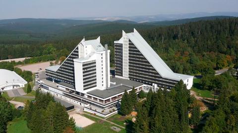 """Der """"Geheimnisvolle Ort"""" begibt sich auf Spurensuche im Ort mit der größten Dichte an Wintersportanlagen auf engstem Raum und dokumentiert eine Zeit, die für viele ein Aufbruch war, mit der Hoffnung auf Wohlstand und westliches Lebensgefühl in einer Oase mitten im Osten. Der Film erzählt auch den wohl spektakulärsten Spionagekrimi der DDR, welcher im nobelsten Hotel vor Ort, dem weit über die Grenzen Oberhofs berühmten PANORAMA eingefädelt wurde. Auf dessen Höhepunkt nahezu die gesamte Auslandsaufklärung der DDR auffliegt und der bis dahin mysteriös-geheimnisumwitterte Chef der HVA: Stasi-General Markus Wolf enttarnt wird."""